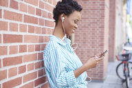 Smiling woman with earphones using cell phone - ABIF00552
