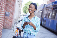 Portrait of laughing woman with earphones and cell phone in the city - ABIF00555