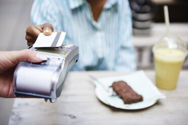 Woman paying by credit card at pavement cafe, close-up - ABIF00564