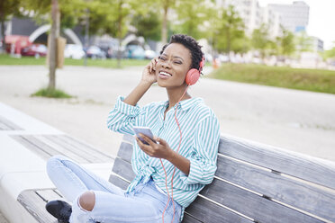 Portrait of young woman sitting on bench listening music with cell phone and headphones - ABIF00579