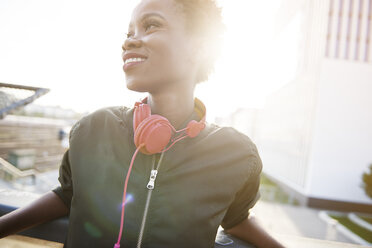 Smiling young woman with headphones at backlight - ABIF00585