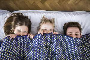 Happy family lying in bed, hiding under blanket - AWF00010