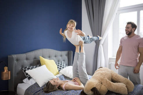 Family playing in bedroom, mother balancing daughter on her feet - AWF00016