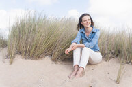 Woman sitting on sand dunes on beach - CUF25952