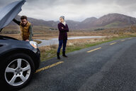 Couple by stalled vehicle at roadside, Connemara, Ireland - CUF25961