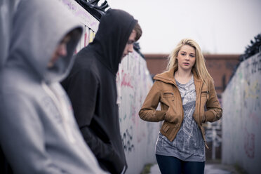 Teenagers standing against wall with graffiti - CUF25982