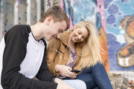 Teenage couple listening to mp3 player against wall with graffiti - CUF25988