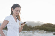 Woman using smartphone on beach - CUF25994