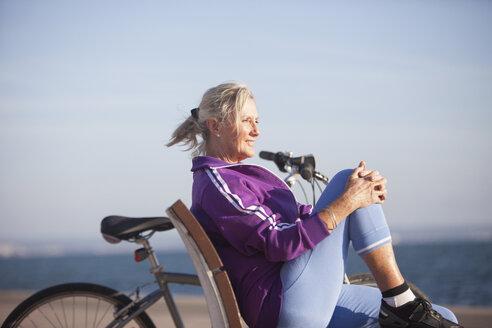 Senior woman enjoying ocean view on bench - CUF26030