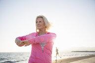 Senior woman stretching by beach - CUF26039