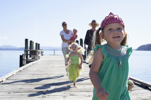 Two mid adult women and daughters strolling and running on pier, New Zealand - CUF26051