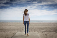Rear view of mid adult woman strolling on beach, Castelldefels, Catalonia, Spain - CUF26060