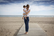 Mid adult woman and toddler daughter on beach, Castelldefels, Catalonia, Spain - CUF26063