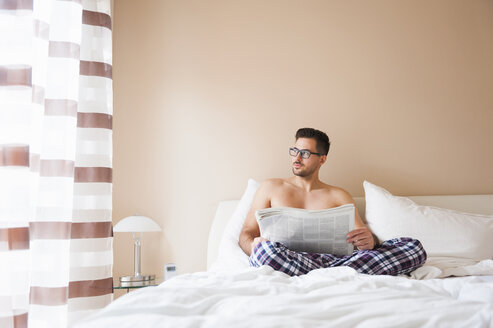 Young man sitting up in bed reading newspaper and gazing out of window - CUF26108