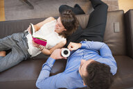 Overhead view of couple reading book and drinking coffee on sofa - CUF26111