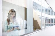 Businesswoman using digital tablet behind office window - CUF26138