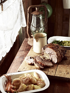Rustic table with roasted goose on chopping board and roasted vegetables - CUF26162