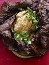Still life of Beggars Chicken wrapped in lotus leaf with coriander garnish - CUF26165
