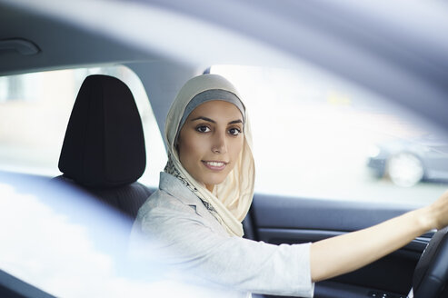 Portrait of young businesswoman wearing hijab driving car - CUF26177