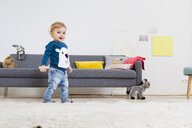 Boy standing beside sofa at home - CUF26231
