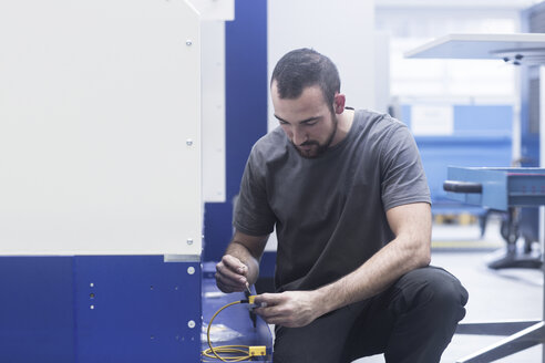 Engineer using allen key in engineering plant - CUF26294