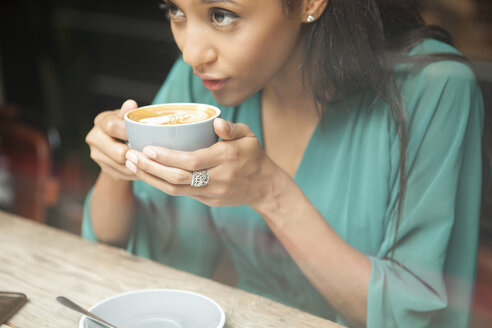 Mid adult woman holding coffee cup looking out of cafe window - CUF26360