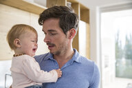 Female toddler crying in fathers arms in kitchen - CUF26432