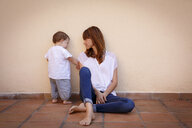 Mid adult woman with curious baby daughter on kitchen floor - CUF26486