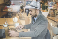 Businessman sitting in front of cafe window using laptop - CUF26582