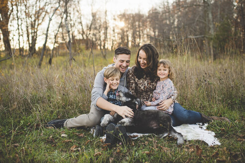 Portrait of young couple with son, daughter and dog in field - CUF26600