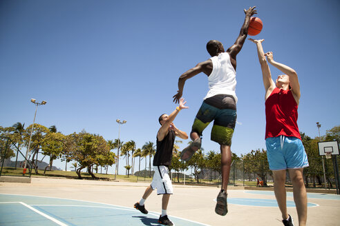Three man basketball team practicing on basketball court - CUF26738