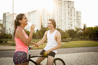 Young couple chatting whilst preparing to cycle in park - CUF26756