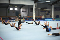 Gymnastics instructor overseeing class practising stretches - CUF26897