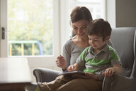 Boy sitting on mother's lap and using digital tablet - CUF26912