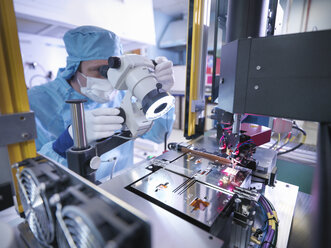 Electronics worker checking component in clean room - CUF26933