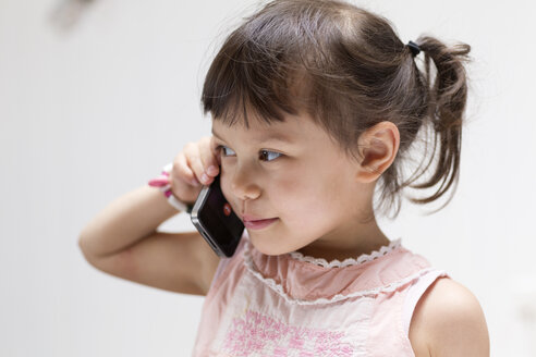 Portrait of smiling little girl on the phone - DRF01742
