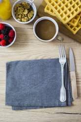 Breakfast table with waffles, wild berries and muesli - GIOF03951