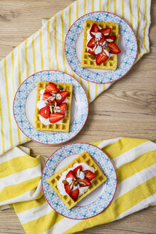 Three plates of waffles garnished with strawberries, Greek yogurt and almonds - GIOF03957
