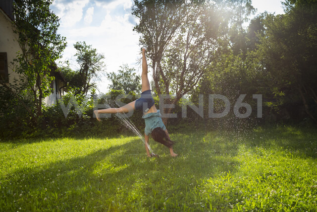 Girl having fun with lawn sprinkler in the garden - LVF07055