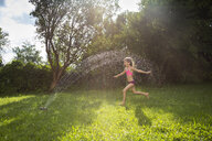 Little girl having fun with lawn sprinkler in the garden - LVF07058