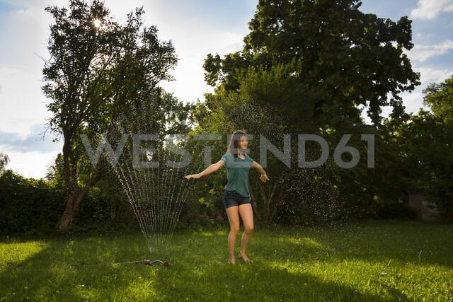 Girl having fun with lawn sprinkler in the garden - LVF07061