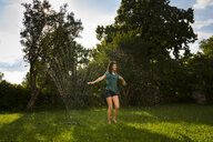 Girl having fun with lawn sprinkler in the garden - LVF07061
