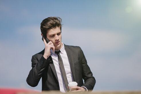 Young businessman chatting on smartphone whilst drinking takeaway coffee - CUF27112