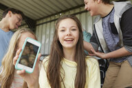 Girl holding up smartphone selfie of friends in shelter - CUF27142