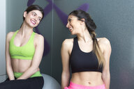 Two young women looking at each other and smiling in gym - CUF27163