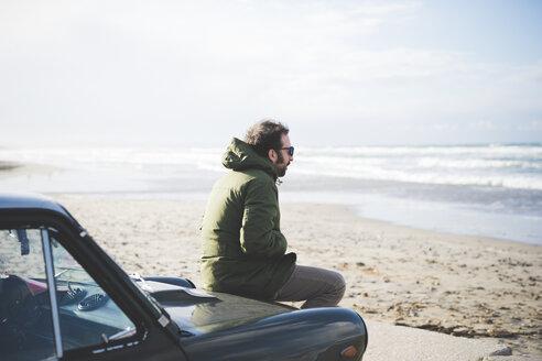 Mid adult man sitting on vintage car on beach, Sorso, Sassari, Sardinia, Italy - CUF27208