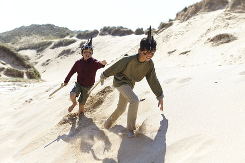Two boys, wearing fancy dress, playing on sand - CUF27265