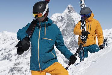 Two men carrying skis in snow, Zermatt, Valais, Switzerland - CUF27283