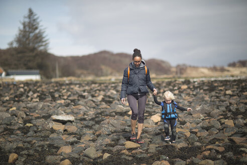 Mother and son holding hands walking on rocks - CUF27346