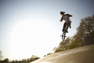 Young man, in mid air, doing stunt on bmx at skatepark - CUF27355